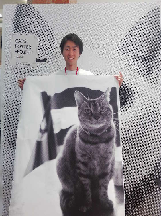 大きな猫ちゃんのポスターを手に、ニンマリ顔のスタッフ