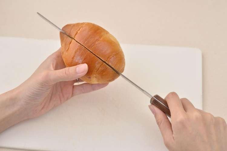 ロールパンに切れ込みを入れ、お好みで中にバターやマヨネーズなどを塗る。
