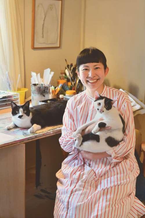 アトリエにて。テンテンを抱っこしたミロコさんと、机の上はボウ。壁には鉄三を描いた作品が