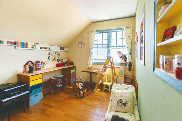 淡い壁色とカラフルな小物がキュートな予備室も、窓辺は猫の特等席