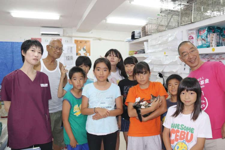 小学生が見学に来院。足立先生と佐上理事長(右)も笑顔で歓迎