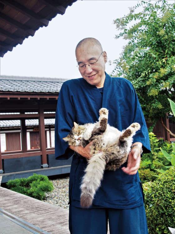 モキチを抱く住職の岡本和幸さん