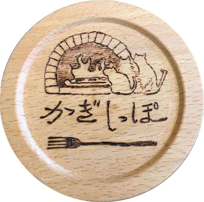 コースターにも描かれているお店のロゴ。暖炉で暖まる猫たちが可愛い