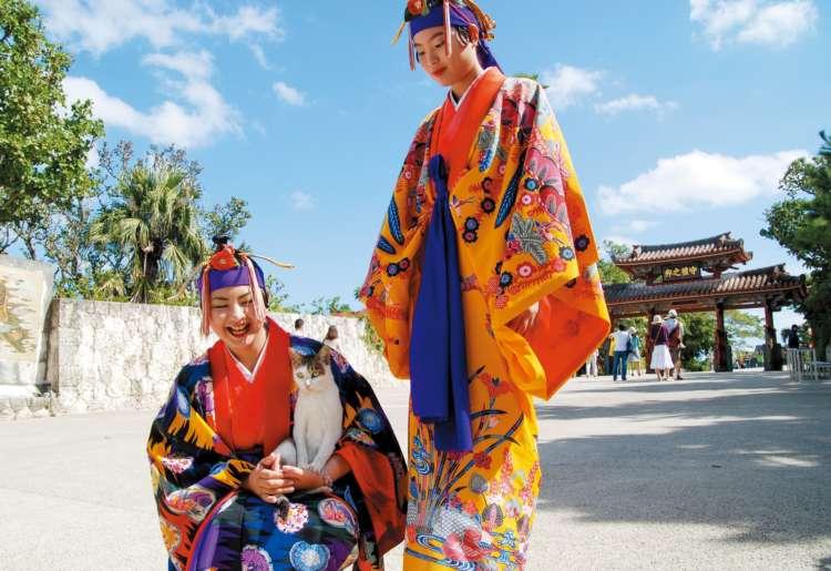 二千円札にも描かれている守礼門の記念写真スポットにて。人懐っこい猫と民族衣装を着たお姉さん